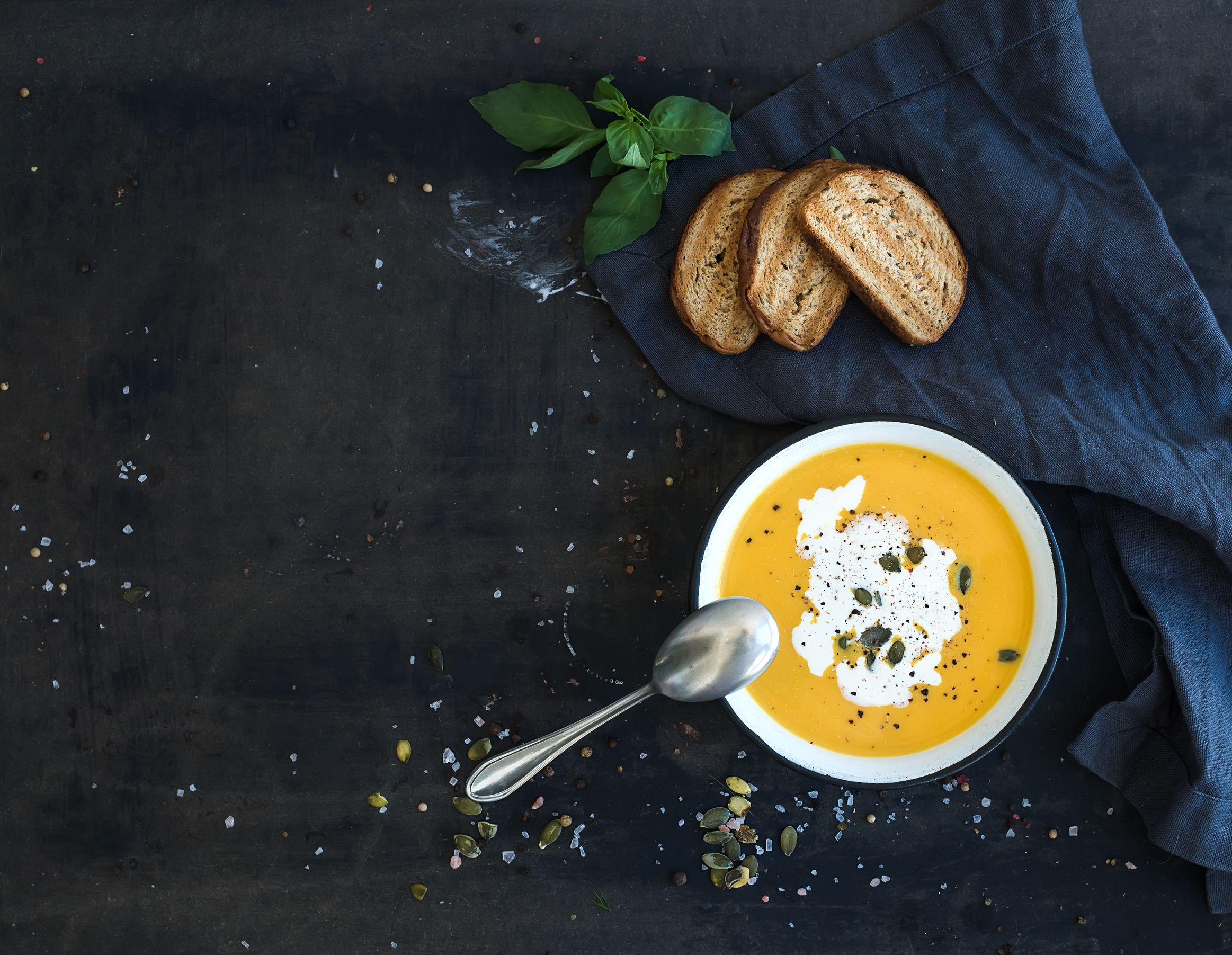 40578087 - pumpkin soup with cream, seeds, bread and fresh basil in rustic metal plate on grunge black background. top view, copy space